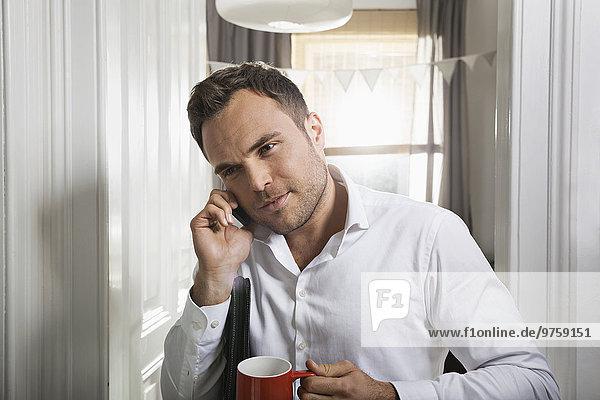 Portrait eines Geschäftsmannes mit Tasse Kaffee telefonieren zu Hause