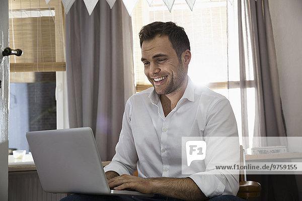 Lachender Mann bei der Arbeit mit dem Laptop in seinem Home-Office