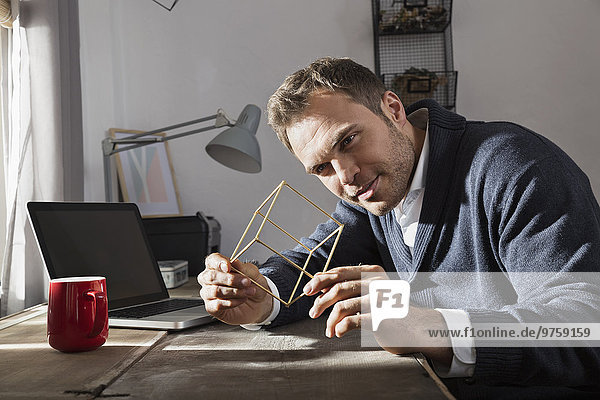Mann mit Modell im Home-Office