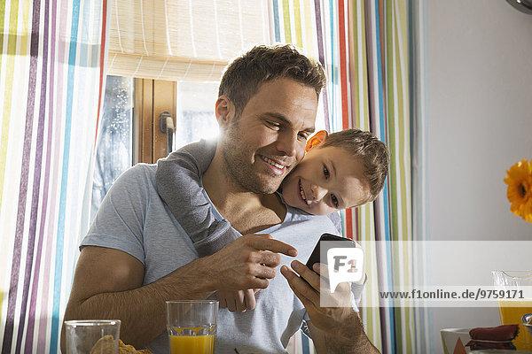 Vater und Sohn betrachten Smartphone