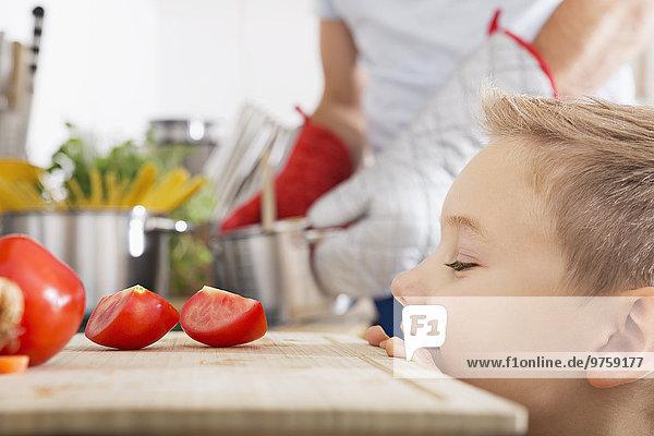 Lächelnder Junge schaut auf Tomatenscheiben auf dem Küchenbrett