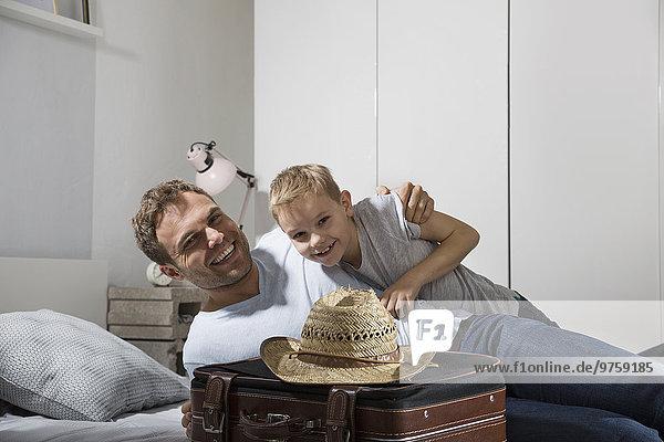 Vater und Sohn auf dem Bett liegend mit Koffer und Strohhut