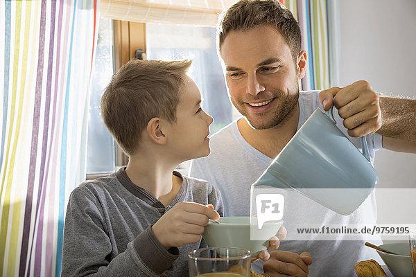 Vater gießt Milch in die Müslischale seines Sohnes
