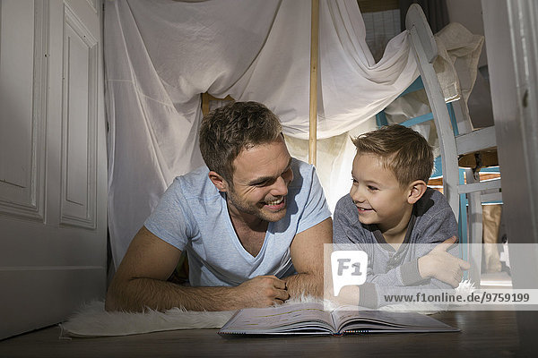 Vater und Sohn haben Spaß im selbstgebauten Zelt zu Hause
