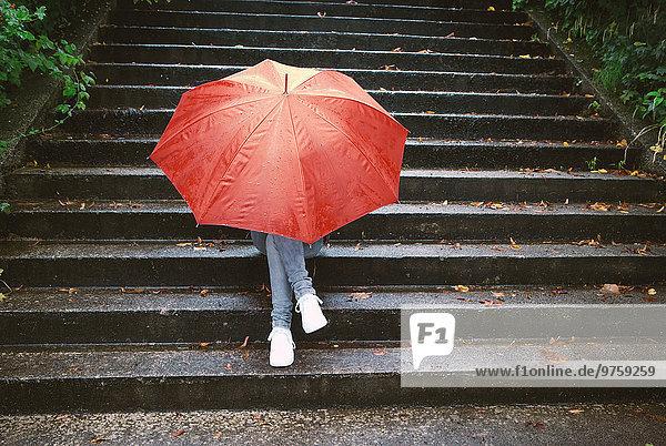 Teenagermädchen sitzt auf einer Treppe und versteckt sich hinter einem roten Regenschirm.
