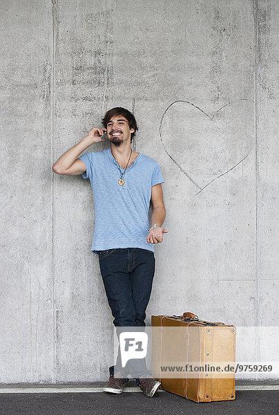 Mann mit Lederkoffer an Betonwand gelehnt telefonieren mit Smartphone Mann mit Lederkoffer an Betonwand gelehnt telefonieren mit Smartphone