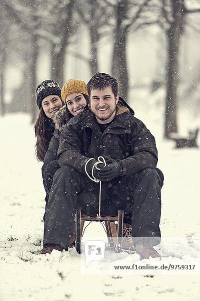 Gruppenfoto von drei Freunden  die im Winter auf dem Schlitten sitzen.