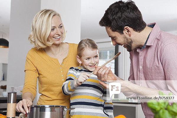 Mutter  Vater und Tochter kochen in der Küche