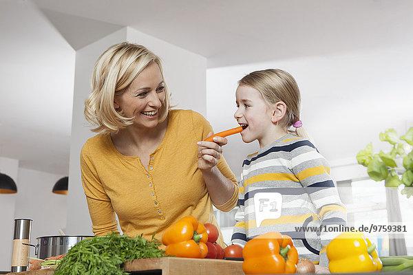 Mutter mit Tochter beim Karottenessen in der Küche