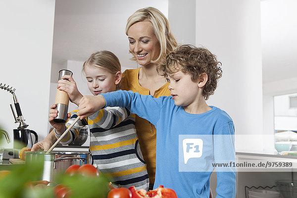 Mutter  Tochter und Sohn kochen in der Küche