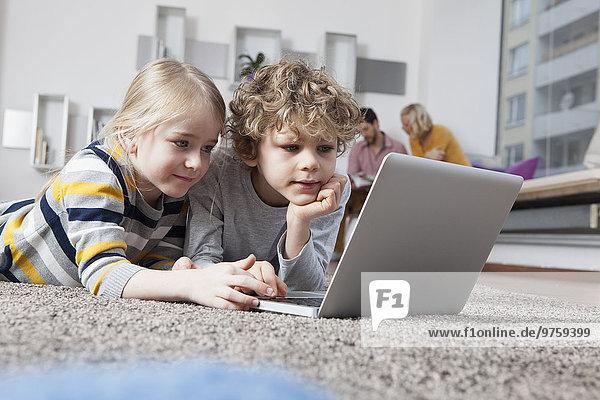 Geschwister auf dem Boden liegend mit Laptop