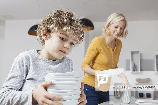 Mutter und Sohn decken den Tisch