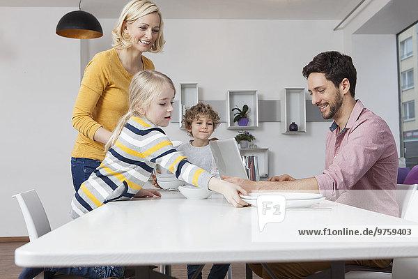 Familie deckt den Tisch mit Vater mit Laptop