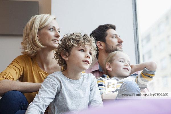 Familie schaut aus dem Fenster
