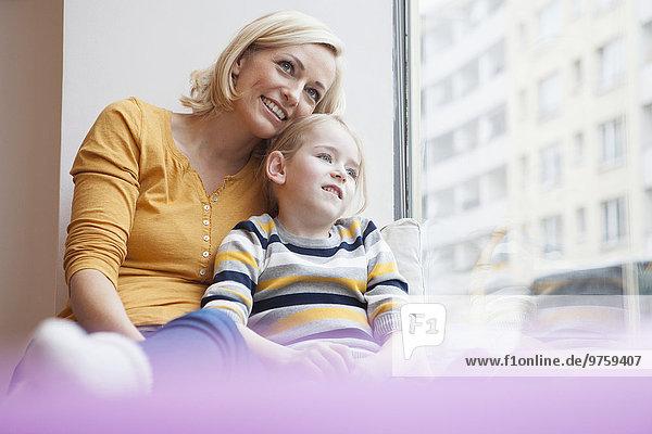 Lächelnde Mutter und Tochter am Fenster