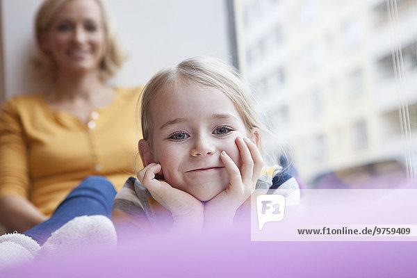 Lächelndes Mädchen mit Mutter im Hintergrund