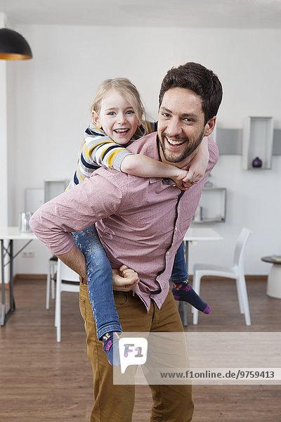 Vater trägt Tochter Huckepack