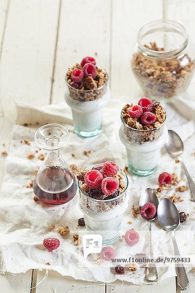 Hausgemachtes glutenfreies Nussgranulat  Himbeeren  griechischer Joghurt und Ahornsirup