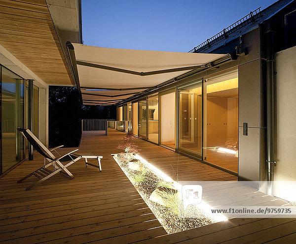 Einfamilienhaus  Holzterrasse mit Markise am Abend