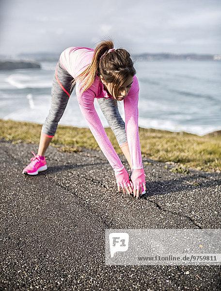Spanien  Gijon  sportliche junge Frau beim Training an der Küste