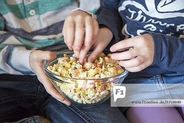 Hände von Jungen und Mädchen  die farbiges Popcorn nehmen Hände von Jungen und Mädchen, die farbiges Popcorn nehmen