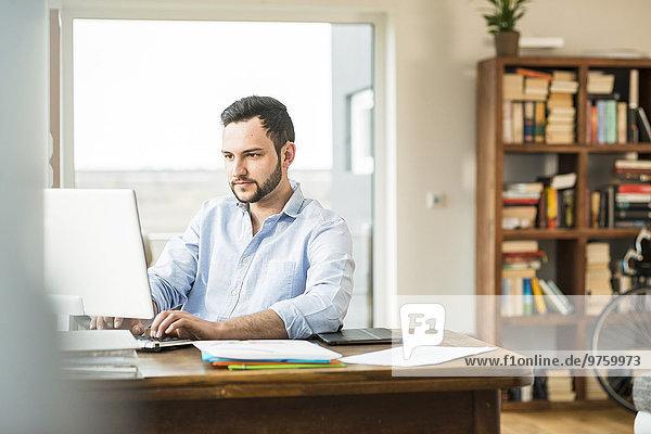 Junger Mann  der zu Hause am Computer arbeitet