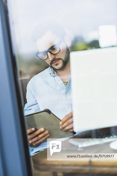 Junger Mann hinter der Fensterscheibe beim Blick auf das digitale Tablett