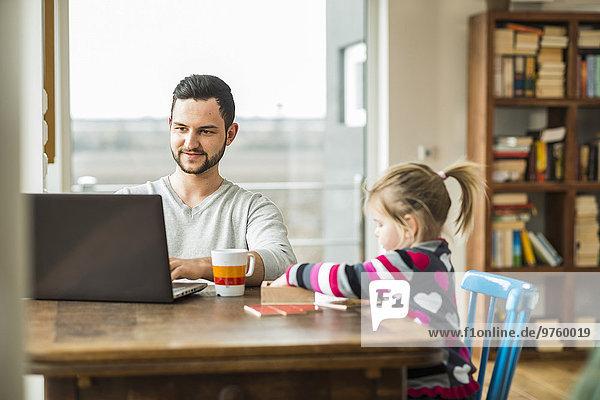 Vater und Tochter mit Laptop und Spiel am Holztisch