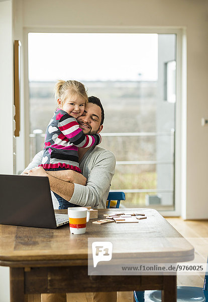 Vater und Tochter umarmen sich am Holztisch