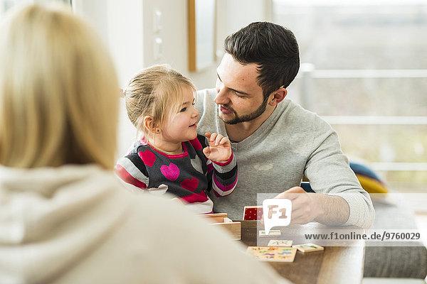Familie spielt ein Spiel am Holztisch