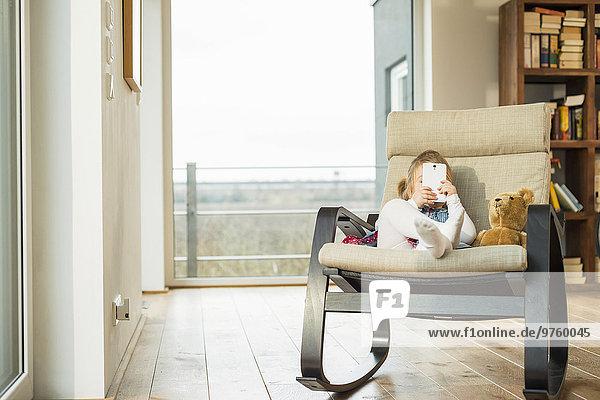Mädchen sitzt im Schaukelstuhl mit Smartphone