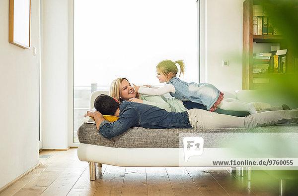 Familie auf Couch übereinander liegend