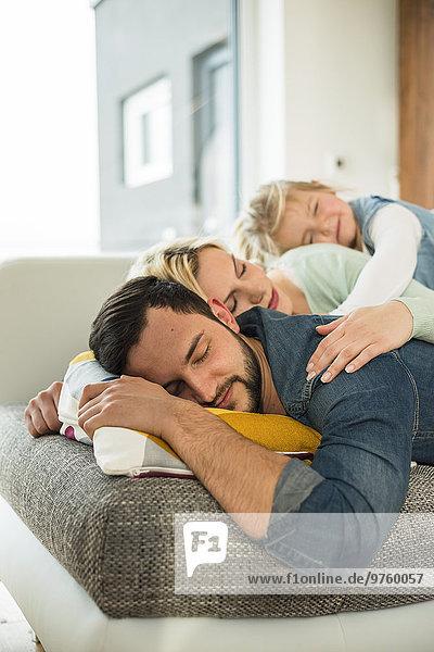 Familie auf der Couch übereinander liegend mit geschlossenen Augen