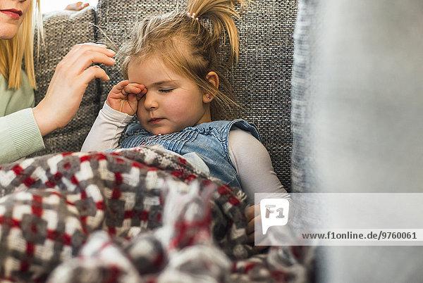 Erschöpftes Mädchen auf der Couch reibt die Augen