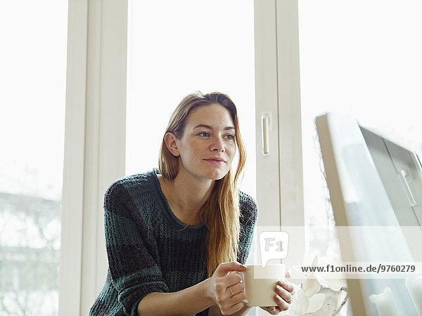 Deutschland  Köln  Junge Frau am Fenster sitzend  Tasse Kaffee haltend Deutschland, Köln, Junge Frau am Fenster sitzend, Tasse Kaffee haltend