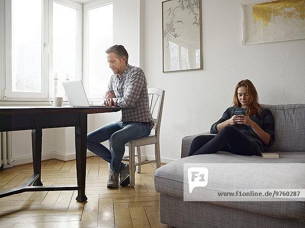 Deutschland  Köln  reifer Mann und Tochter und Zuhause mit Laptop und Smartphone