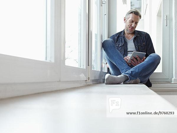 Deutschland  Köln  Erwachsener Mann am Fenster sitzend mit digitalem Tablett Deutschland, Köln, Erwachsener Mann am Fenster sitzend mit digitalem Tablett