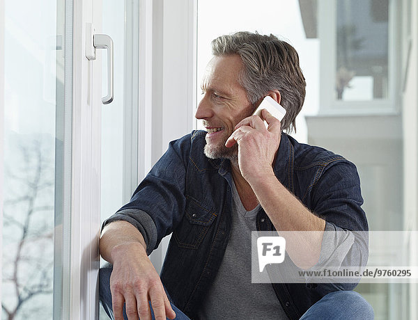Deutschland  Köln  Erwachsener Mann am Fenster sitzend mit Smartphone