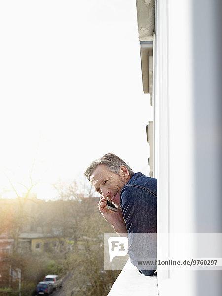 Deutschland  Köln  Mann aus dem Fenster gelehnt mit dem Handy Deutschland, Köln, Mann aus dem Fenster gelehnt mit dem Handy