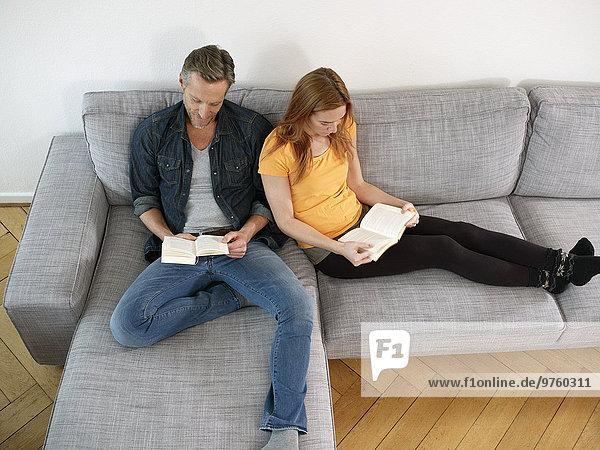 Erwachsener Mann mit erwachsener Tochter beim Lesen auf dem Sofa