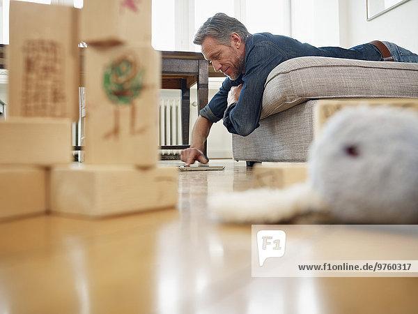 Erwachsener Mann auf dem Sofa liegend mit digitalem Tablett Erwachsener Mann auf dem Sofa liegend mit digitalem Tablett
