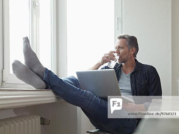 Deutschland  Köln  reifer Mann am Fenster sitzend mit Laptop  Füße oben Deutschland, Köln, reifer Mann am Fenster sitzend mit Laptop, Füße oben