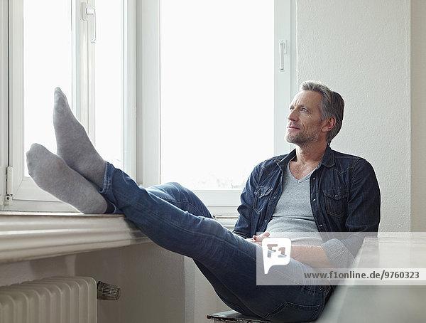 Deutschland  Köln  reifer Mann am Fenster sitzend  aus dem Fenster schauend Deutschland, Köln, reifer Mann am Fenster sitzend, aus dem Fenster schauend