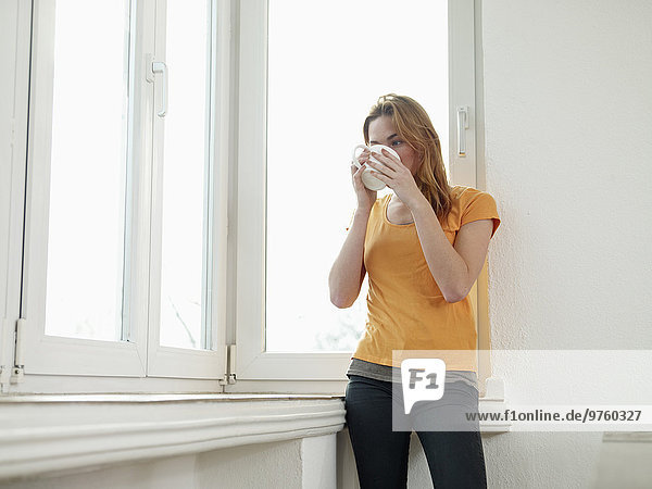 Deutschland  Köln  Junge Frau steht am Fenster  schaut hinaus Deutschland, Köln, Junge Frau steht am Fenster, schaut hinaus