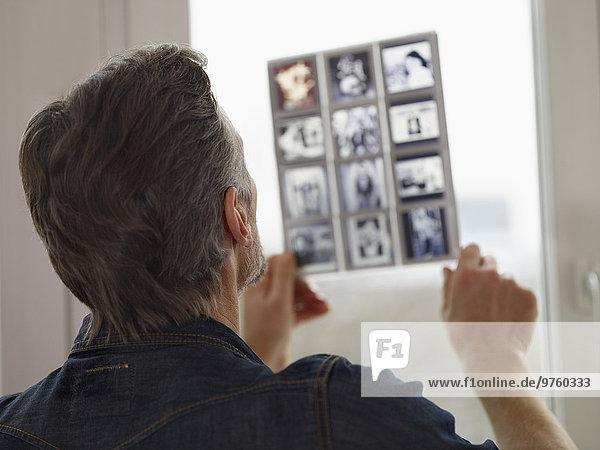 Reifer Mann beim Betrachten alter Dias Reifer Mann beim Betrachten alter Dias