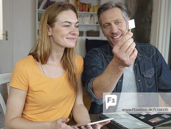 Reifer Mann und junge Frau beim Durchsehen der Briefmarkensammlung Reifer Mann und junge Frau beim Durchsehen der Briefmarkensammlung