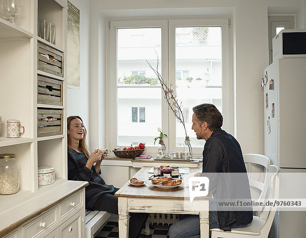 Junge Frau und reifer Mann sitzen in der Küche und frühstücken.