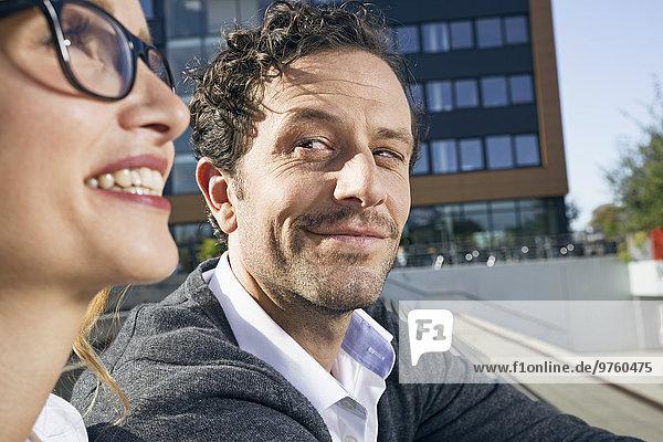 Porträt eines lächelnden Geschäftsmannes  der seine Kollegin beobachtet.