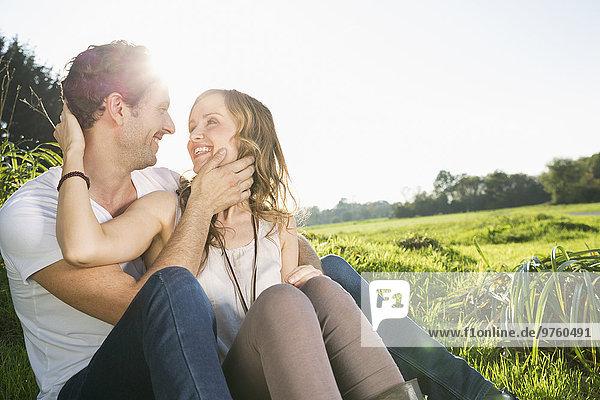 Glückliches Paar von Angesicht zu Angesicht auf einer Wiese sitzend