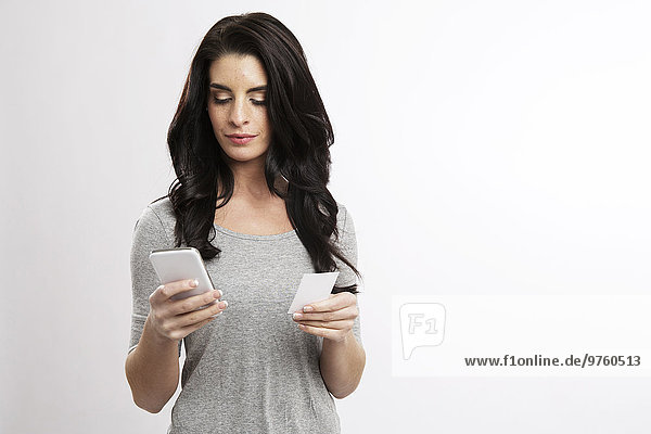 Portrait of young woman with smartphone and business card